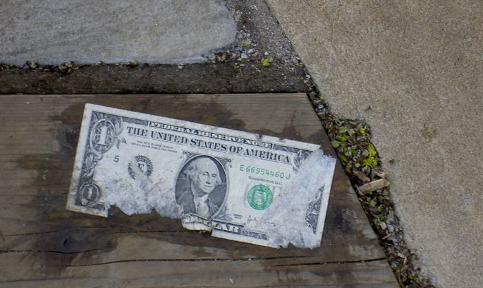 a dollar bill, glued to wood planking on the ground