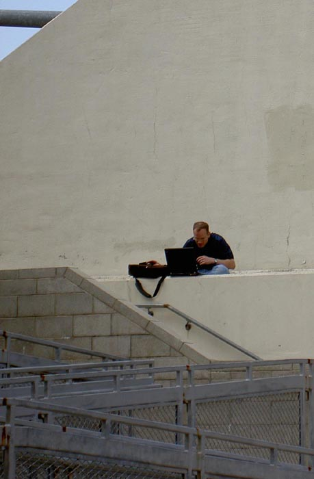 man using laptop against painted concrete, vertical crop