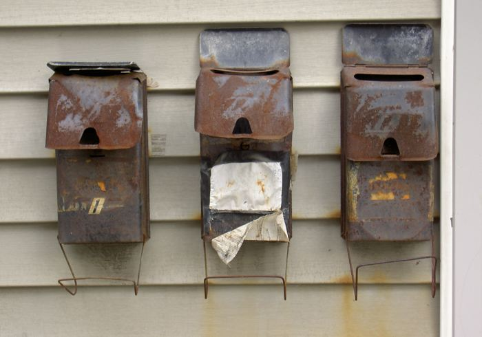 three old mailboxes on a vinyl wall