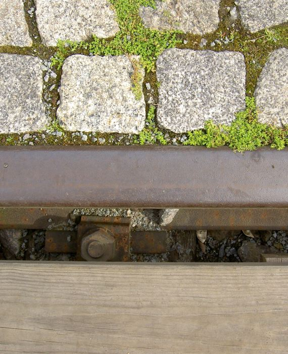 a rail between cobble stones and wood planking