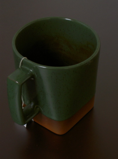 a green-glazed mug with bare clay at the bottom, square in cross section at the base and circular at the top