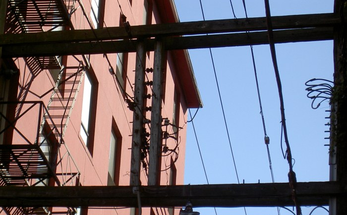 sky and a red building through shadowy iron and woodwork