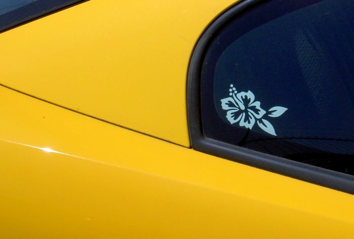 yellow car exterior with flower sticker and reflections