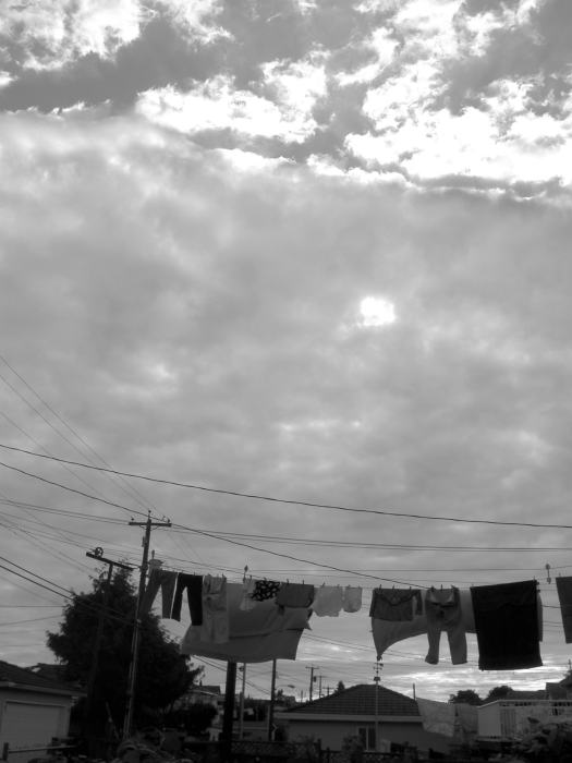 laundry and lines below sun-through-cloudy sky