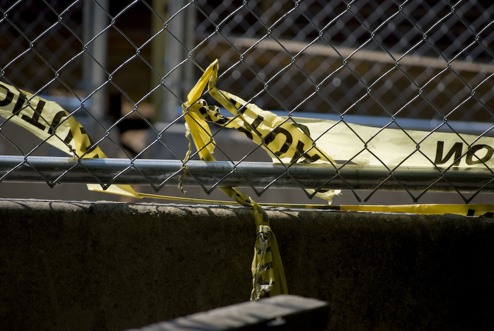 caution tape woven through a barrier and fence near a construction site