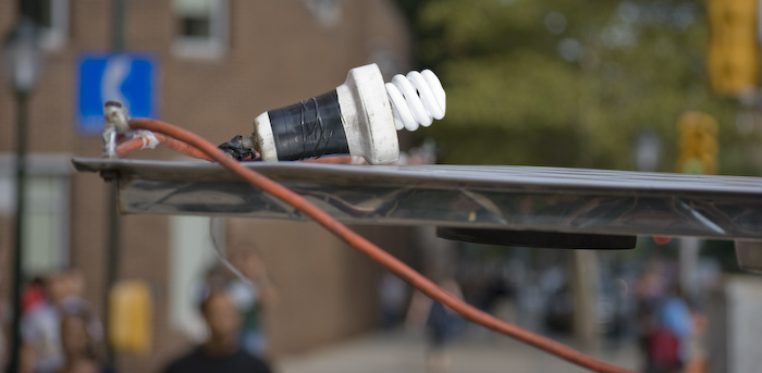 coiled bulb on an extension cord, on a food cart awning
