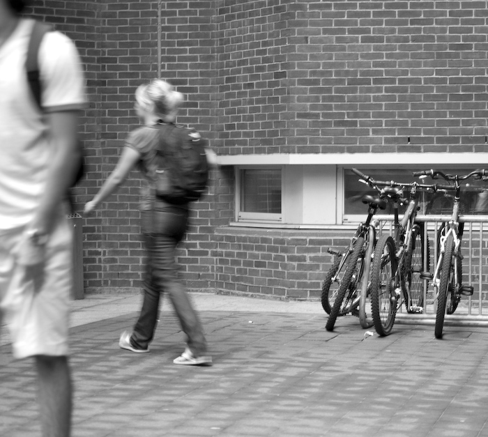 pedestrians passing a bike rack and low window