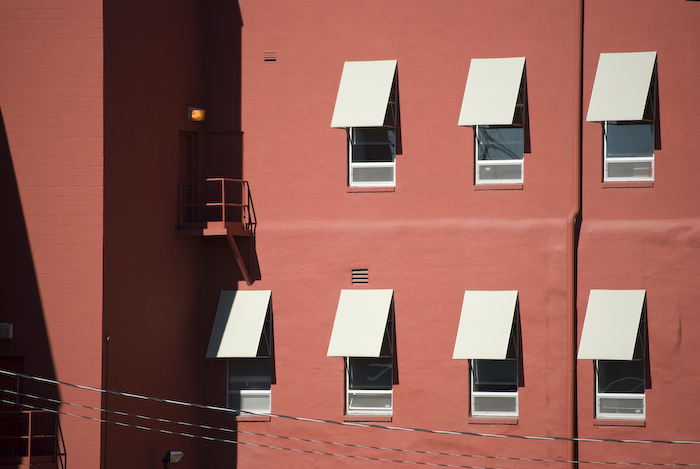 red building in strong sunlight with window awnings