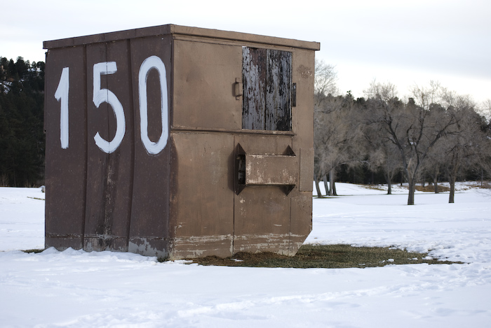 garbage dumpster in snowy golf course