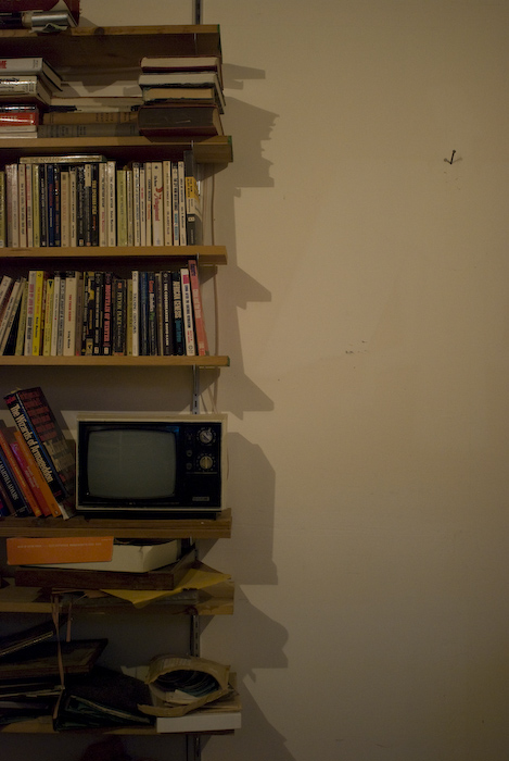 tv and old books on shelves in artificial light, next to empty wall