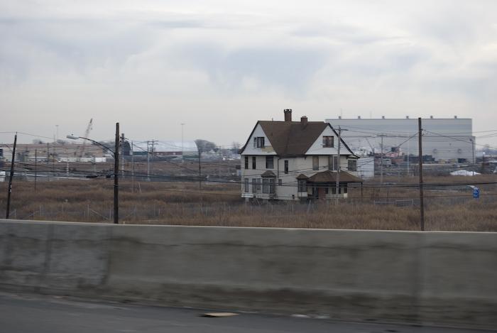 disheveled house among power lines and urban waste