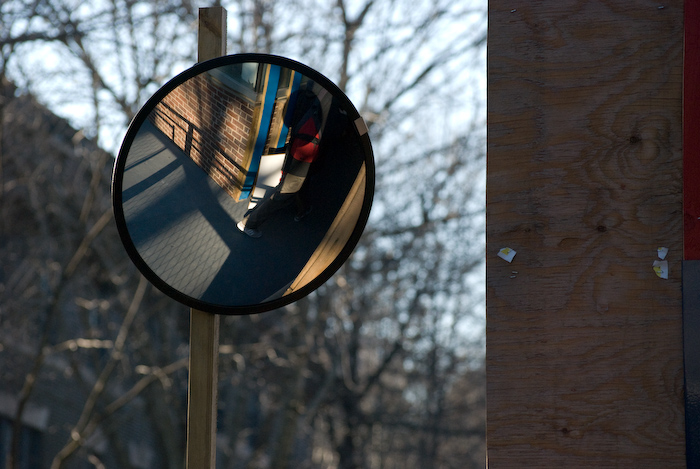 convex mirror on the walkway around the corner of Addams, with a pedestrian