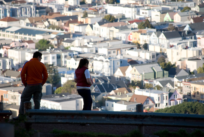 two people looking out over San Francisco from a hilltop