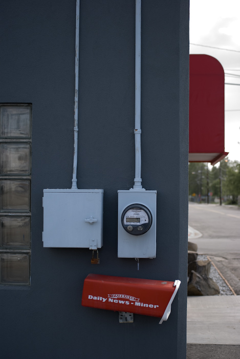 utilities and a mailbox on a gray building