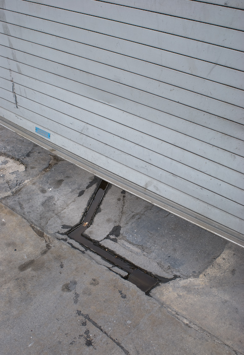 puddle in a depression in concrete, under a roll-down metal door