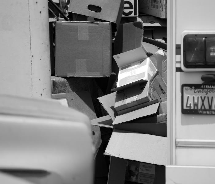 cascade of cardboard boxes seen through a gap between vehicles