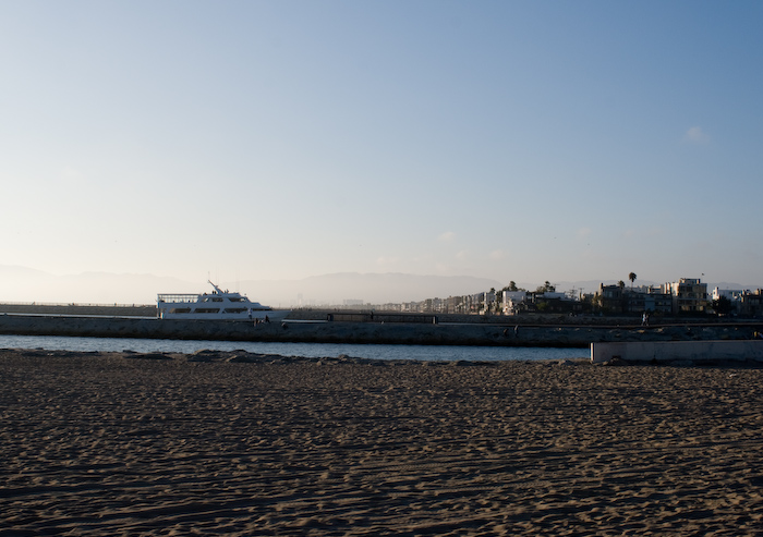 boat against beach and mountains with smog