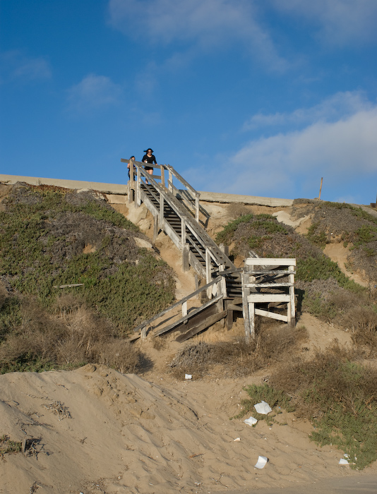girls at the top of a broken staircase at the beach
