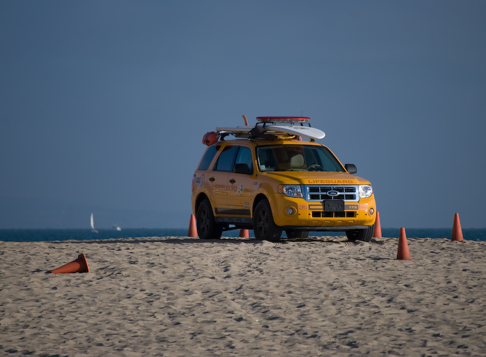 yellow lifeguard car on beach with cones