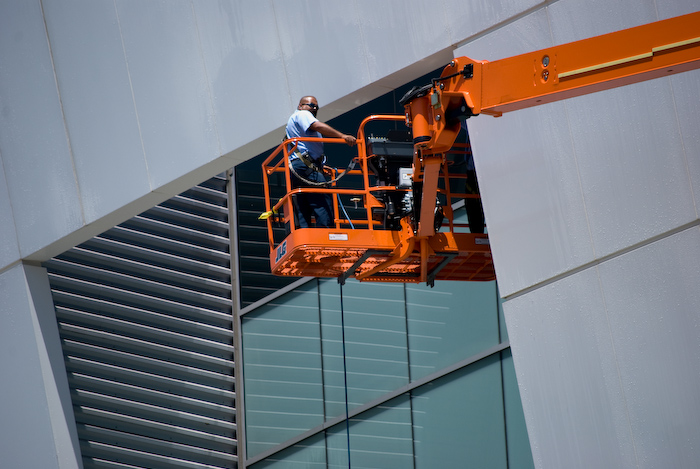 man on cherry-picker cleaning recessed window