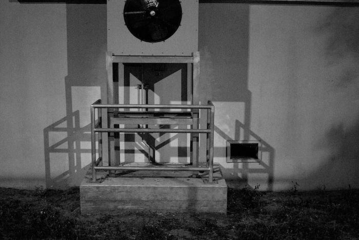 shadows behind an air conditioning unit at night