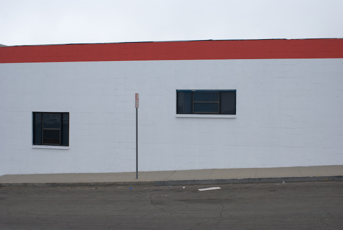 windows and sign with a red stripe ona building