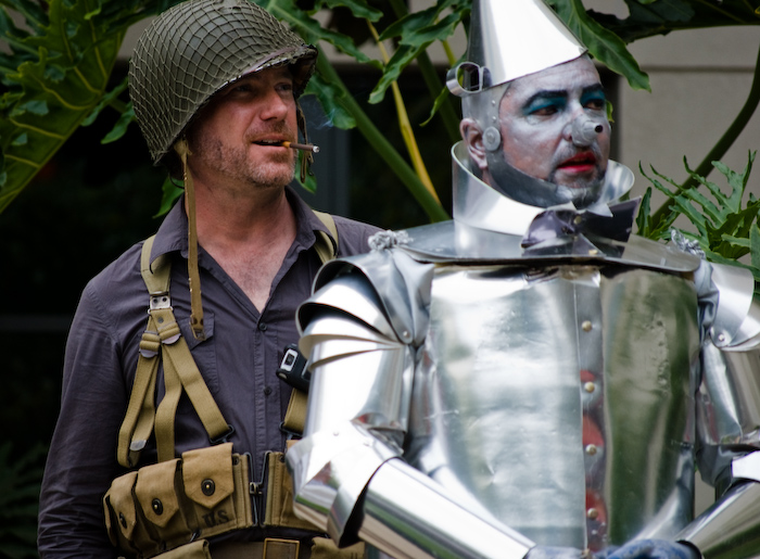 man in army costume smoking behind tin man