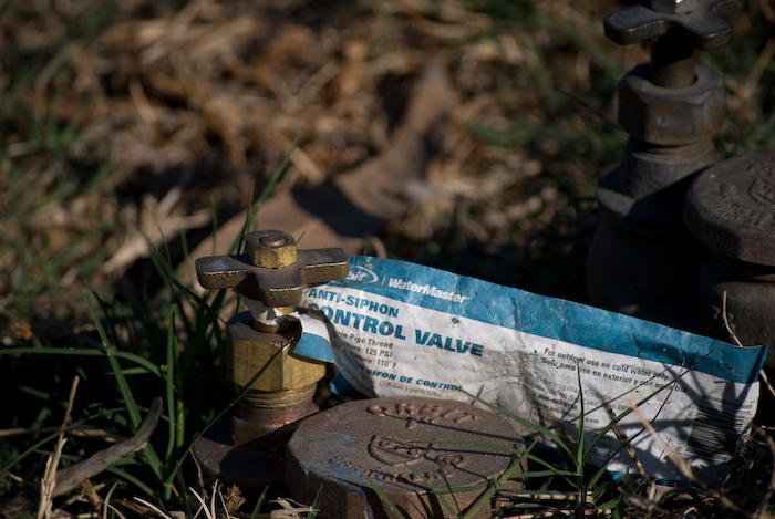 pipe valves in grass with label attached