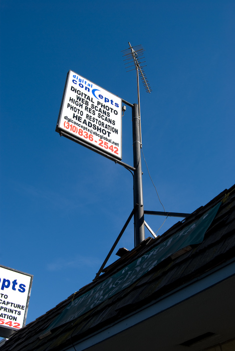 signs on angled rooftop with antenna