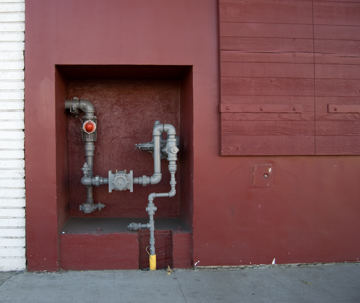 inset with pipe in maroon concrete wall