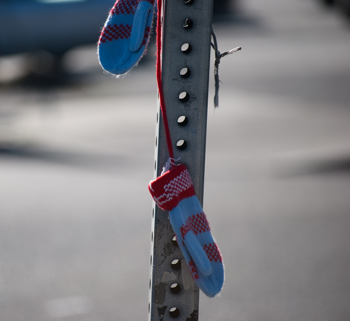 mittens hanging from a street sign post