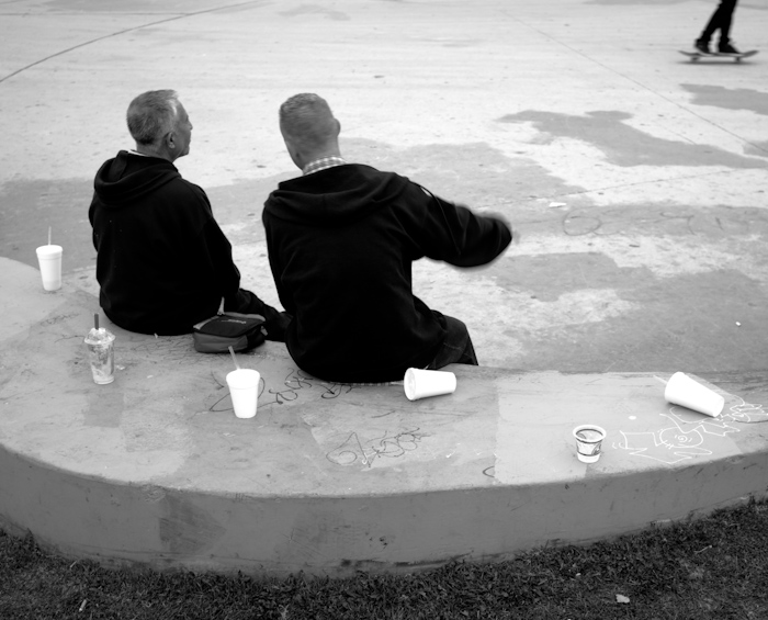 men on bench with cups at skate park