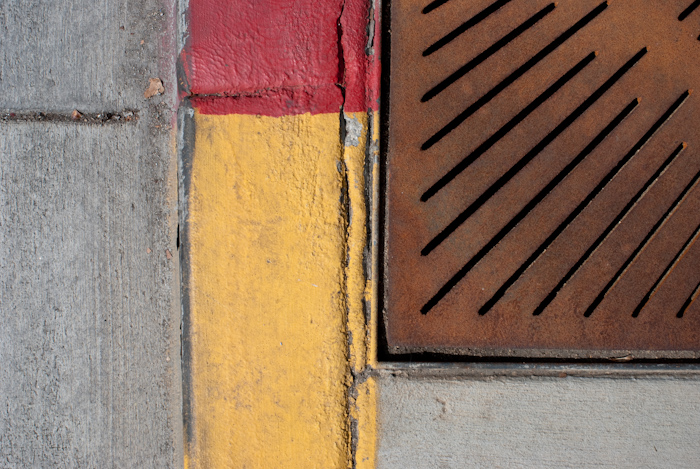 red and yellow curb with rusted grating