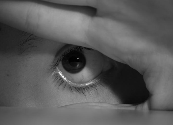 eye behind hand and desk edge
