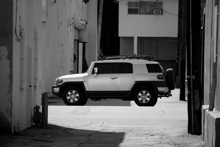 SUV framed in alleyway