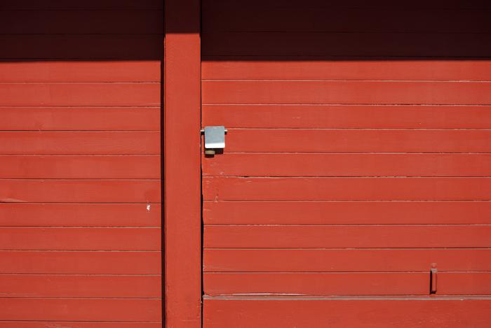 red garage door with metal lock cover