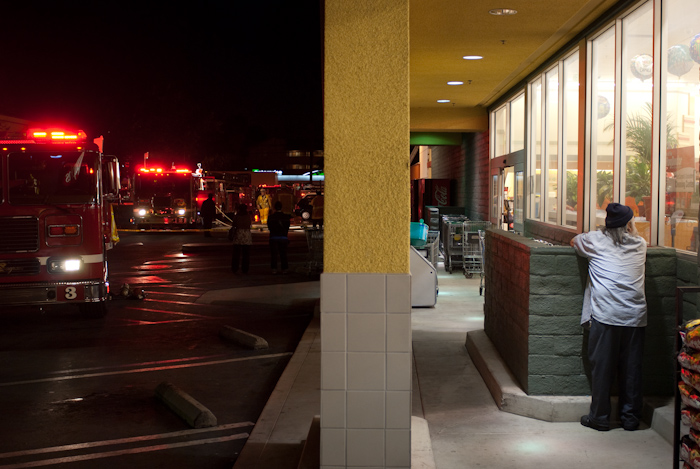 grocery store front sidewalk and fire trucks with pillar in foreground