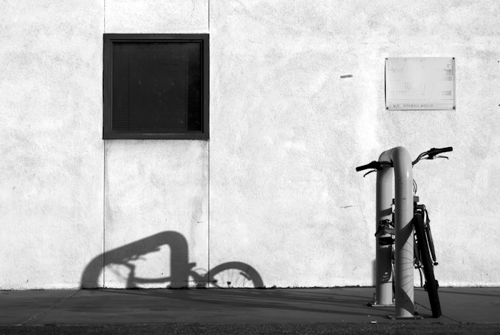 bicycle locked to post with wall and shadow