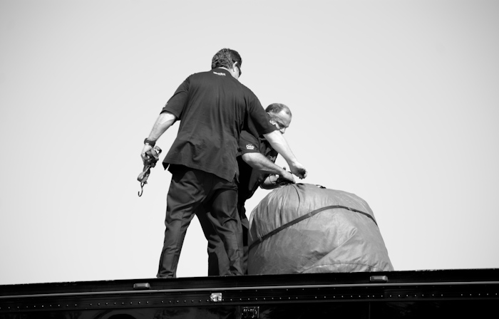 men with bag on trailer roof