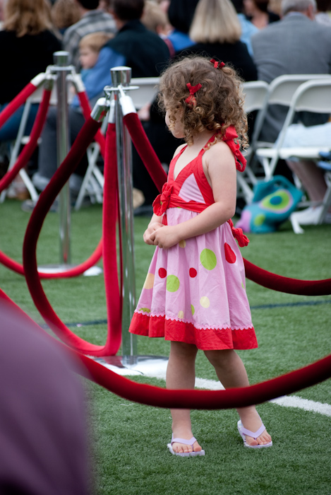girl in red and pink dress in aisle among red velvet ropes