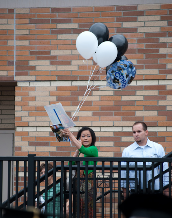 woman with papers and balloons on stairs