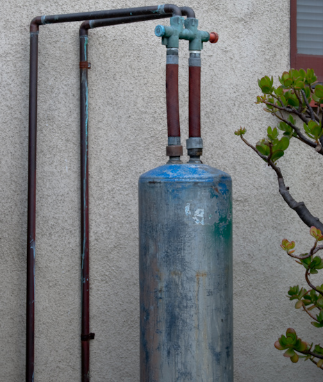 cylinder with pipes against wall