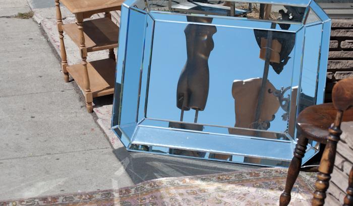 mannequins in mirror on sidewalk