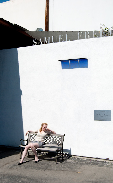 Katrina on bench on phone with walls, blue, and shadow