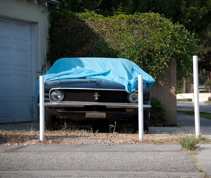 blue mustang under cover from front past poles
