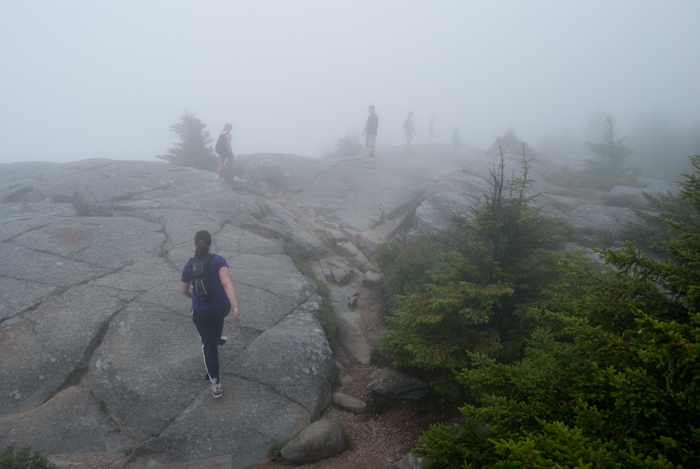 figures hiking over rocks with fog