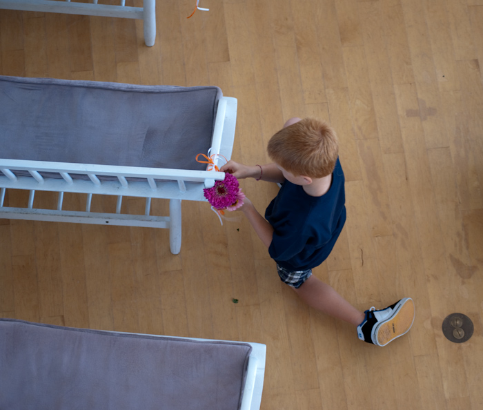 young boy tying flowers to pews