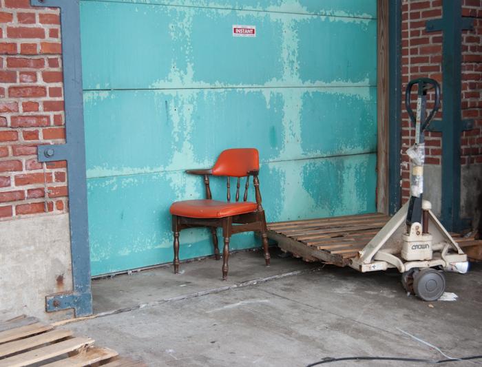 orange chair in front of turquoise garage door