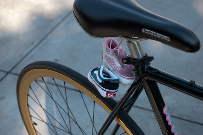 small shoes attached under bicycle saddle