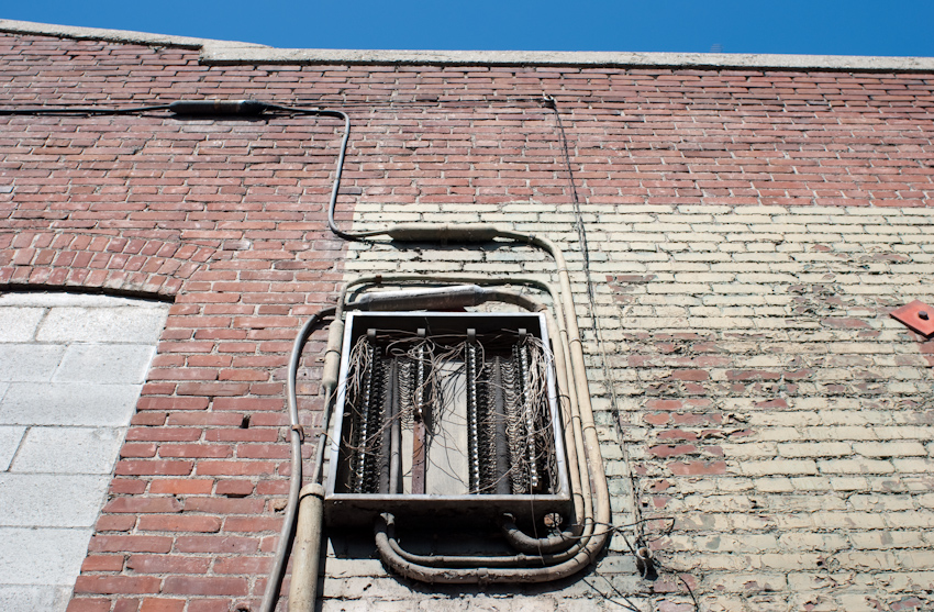 open electrical panel on brick wall with sky